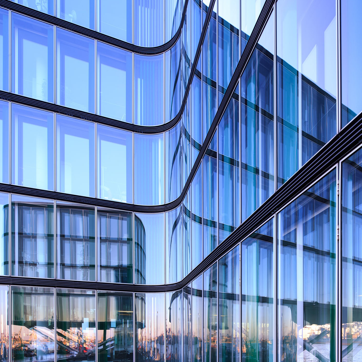 Reflection of the Hamburg harbor i a glass facade of a modern office building.